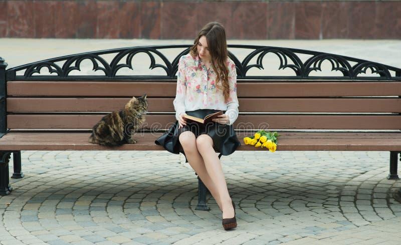 Mädchen, das ein Buch mit einer Katze auf einer Bank in der Stadt liest lizenzfreie stockbilder