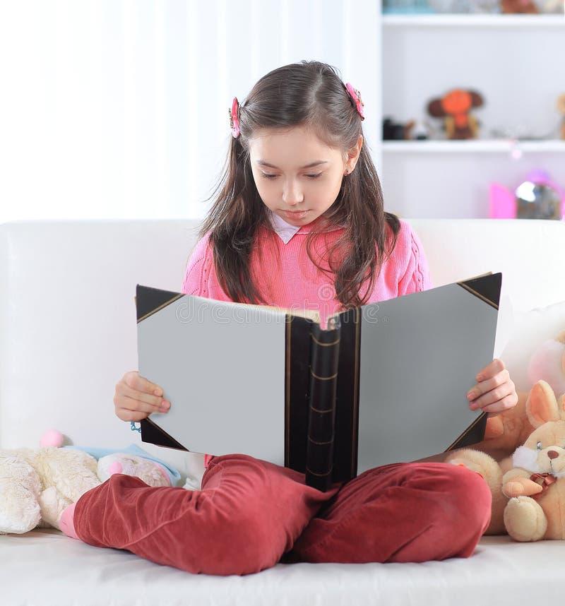Mädchen, das ein Buch sitzt auf der Couch in der Kindertagesstätte liest lizenzfreies stockfoto
