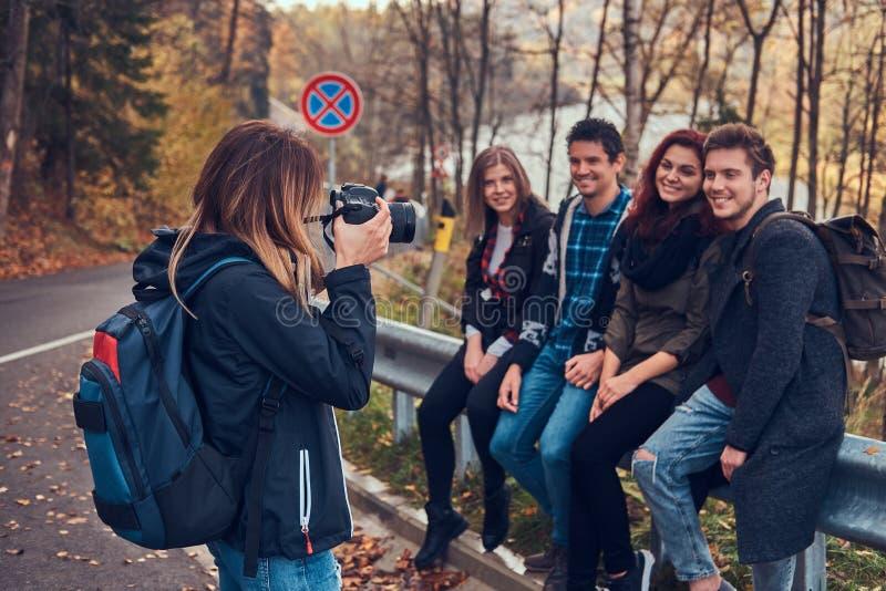Mädchen, das ein Foto ihrer Freunde macht Gruppe junge Freunde, die auf Leitschiene nahe Straße sitzen stockbild