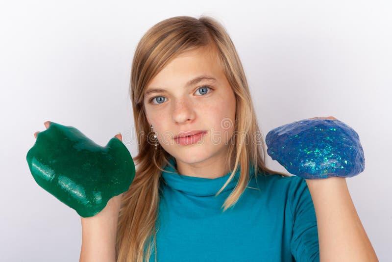 Mädchen, das ein Grün und einen blauen Schlamm hält lizenzfreies stockfoto