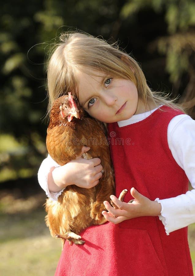 Mädchen, das ein Huhn umarmt stockfoto