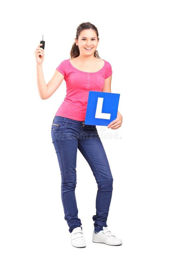 Mädchen, das ein L Zeichen und einen Autoschlüssel hält stockbild