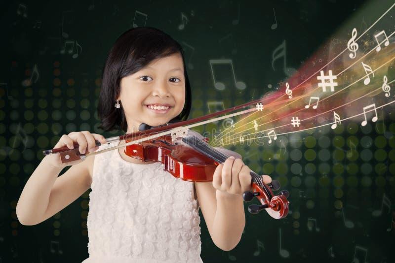 Mädchen, das ein Lied mit einer Violine spielt lizenzfreies stockbild