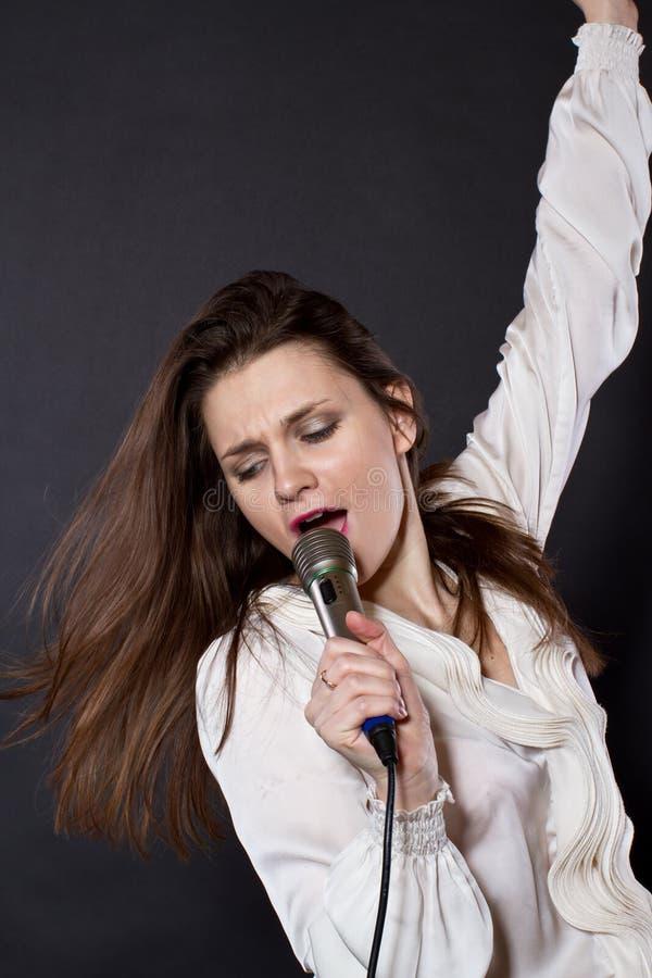 Mädchen, das in ein Mikrofon singt stockbild