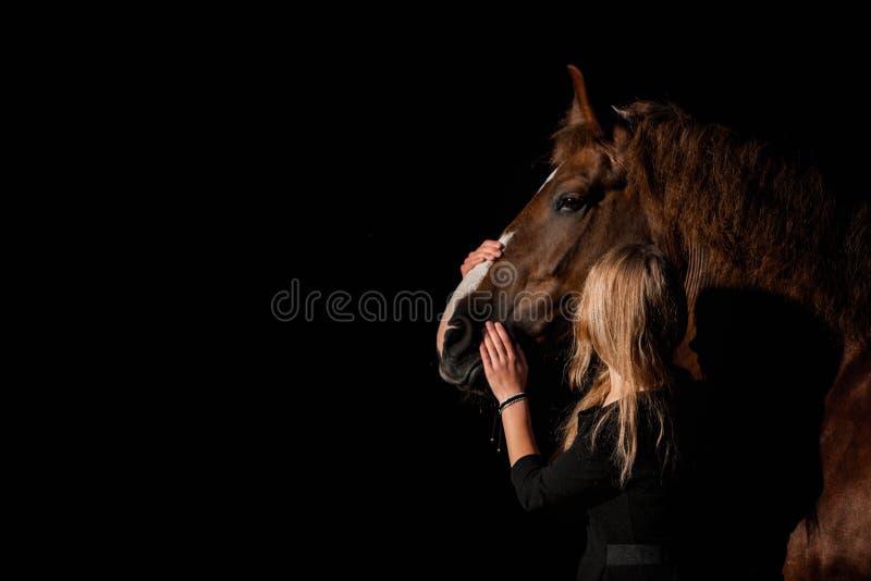 Mädchen, das ein Pferd auf einem dunklen Hintergrund umarmt stockfotos