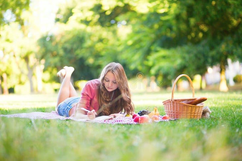 Mädchen, das ein Picknick hat und in ihr Tagebuch schreibt lizenzfreie stockfotos