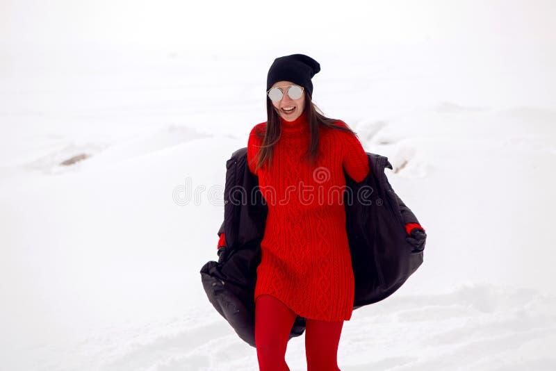 Mädchen, das in ein schneebedecktes Feld in einer Jacke läuft lizenzfreie stockfotos