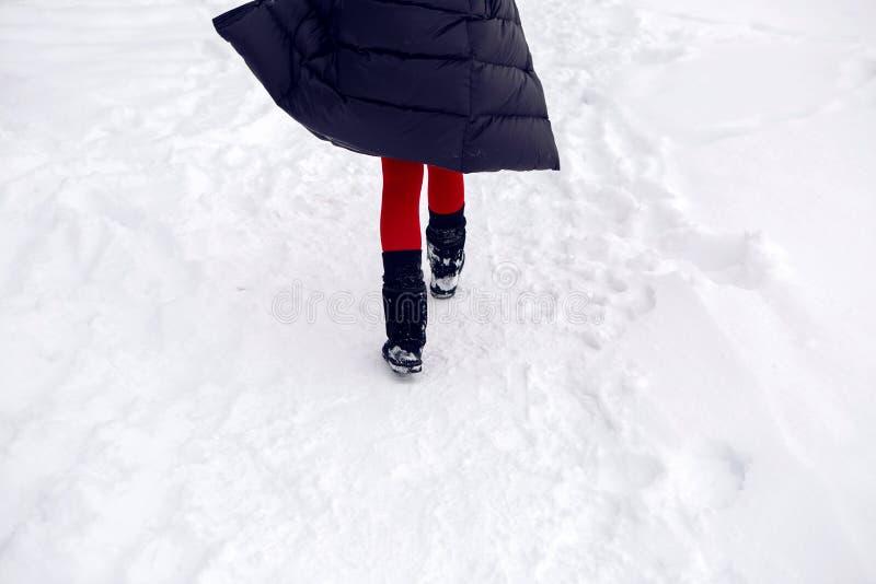 Mädchen, das in ein schneebedecktes Feld in einer Jacke läuft stockfotos