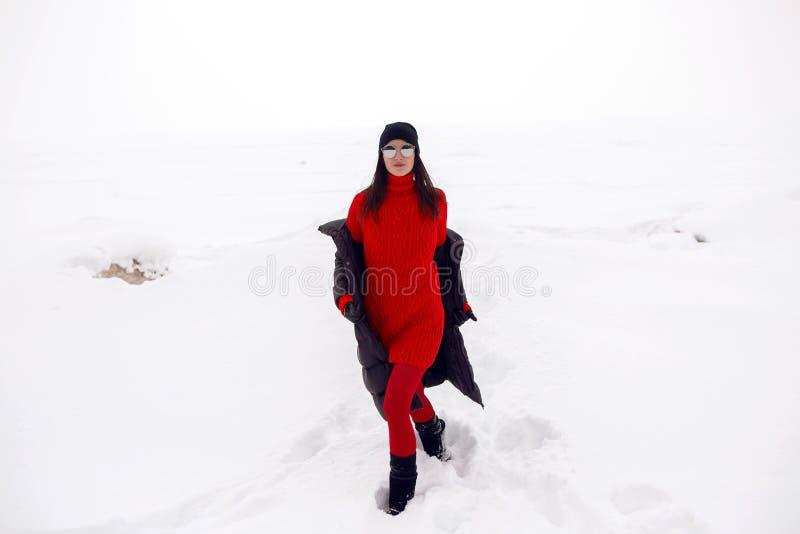 Mädchen, das in ein schneebedecktes Feld in einer Jacke läuft lizenzfreies stockbild