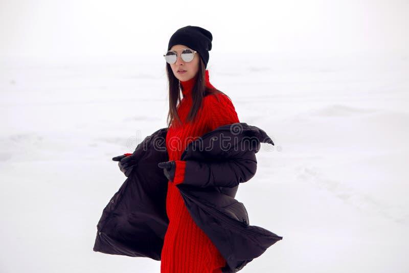 Mädchen, das in ein schneebedecktes Feld in einer Jacke läuft lizenzfreie stockbilder
