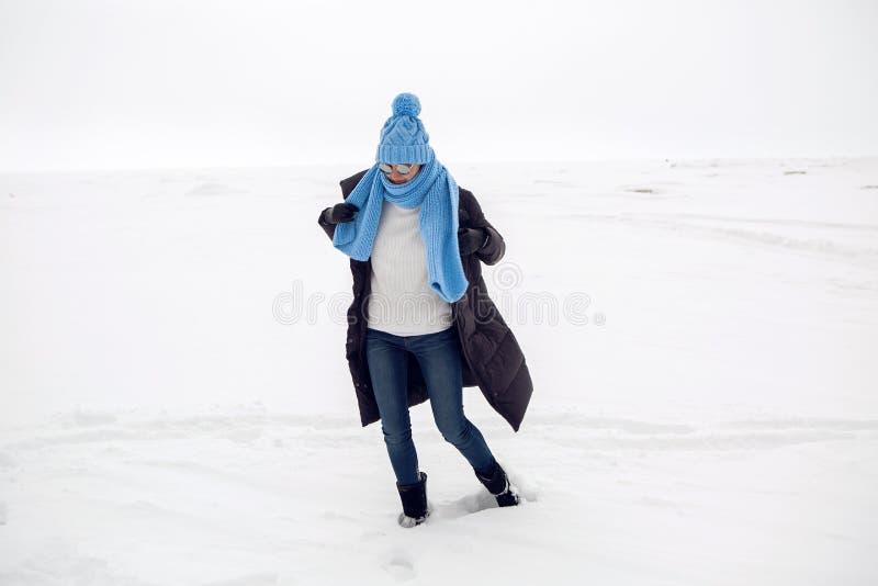 Mädchen, das in ein schneebedecktes Feld in einer Jacke läuft lizenzfreies stockfoto