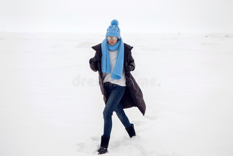 Mädchen, das in ein schneebedecktes Feld in einer Jacke läuft stockbilder