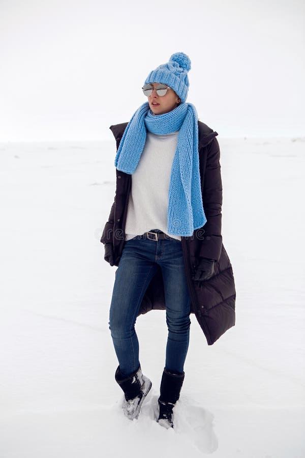 Mädchen, das in ein schneebedecktes Feld in einer Jacke läuft stockbild