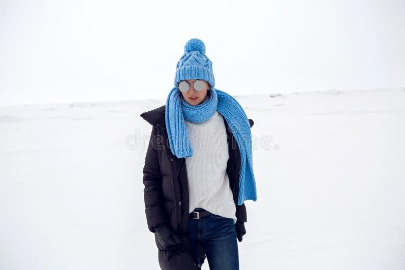 Mädchen, das in ein schneebedecktes Feld in einer Jacke läuft stockfotografie