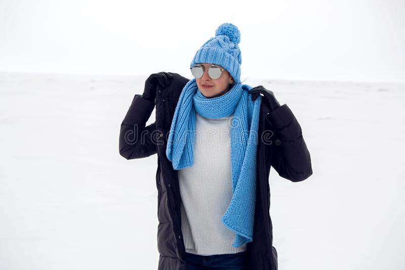 Mädchen, das in ein schneebedecktes Feld in einer Jacke läuft stockfoto