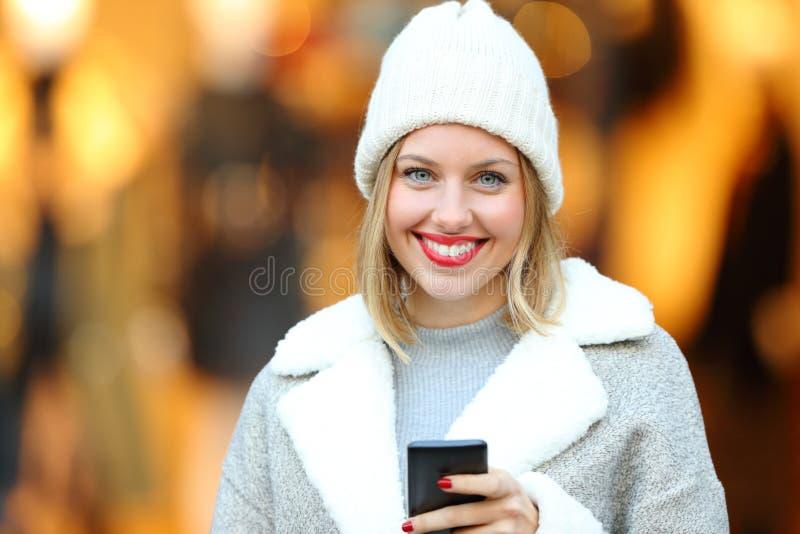 Mädchen, das ein Telefon hält und Sie im Winter betrachtet lizenzfreies stockfoto