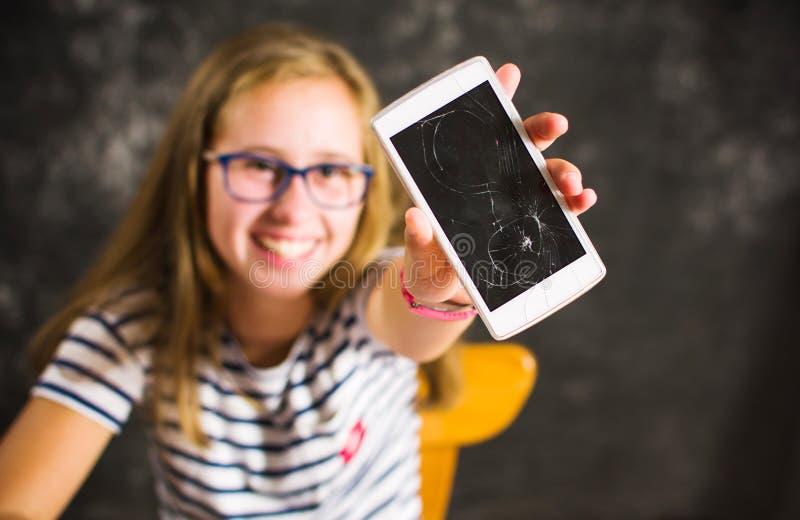 Mädchen, das ein Telefon mit defektem Schirm zeigt lizenzfreies stockbild