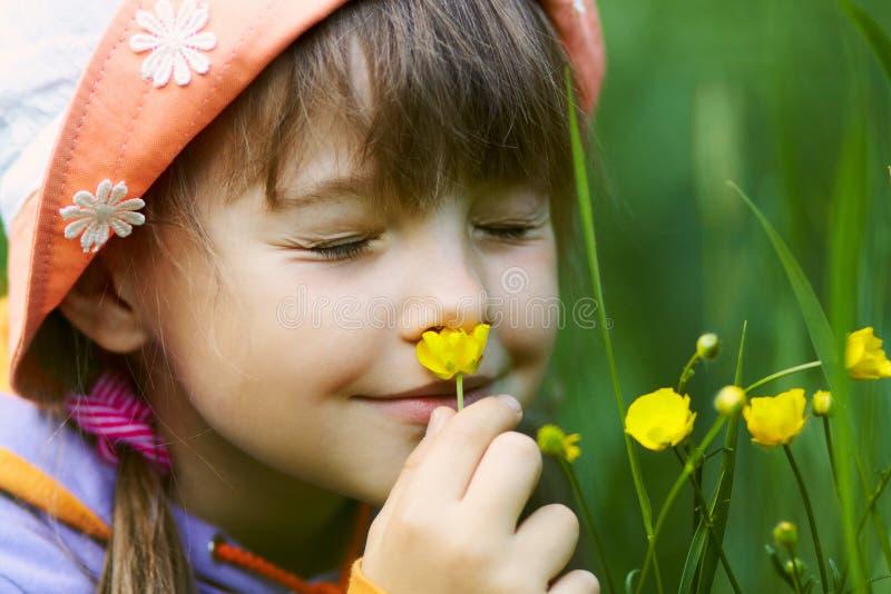 Mädchen, das eine Blume riecht stockfotografie