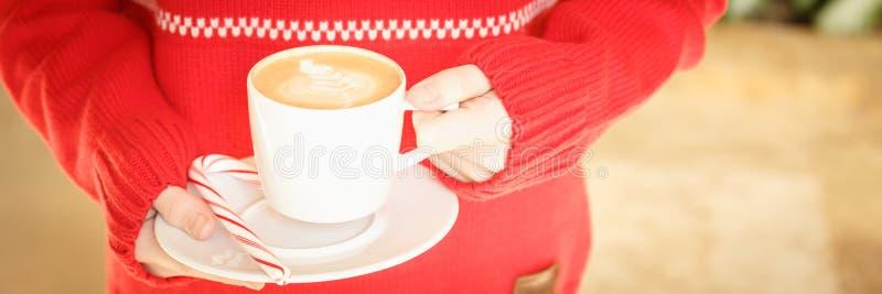 Mädchen, das eine Cappuccinoschale mit Zuckerstange hält Konzept von Christus stockbild