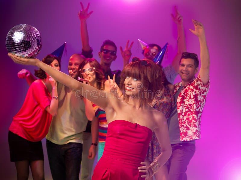 Mädchen, das eine Discokugel an der Partei anhält lizenzfreie stockfotos