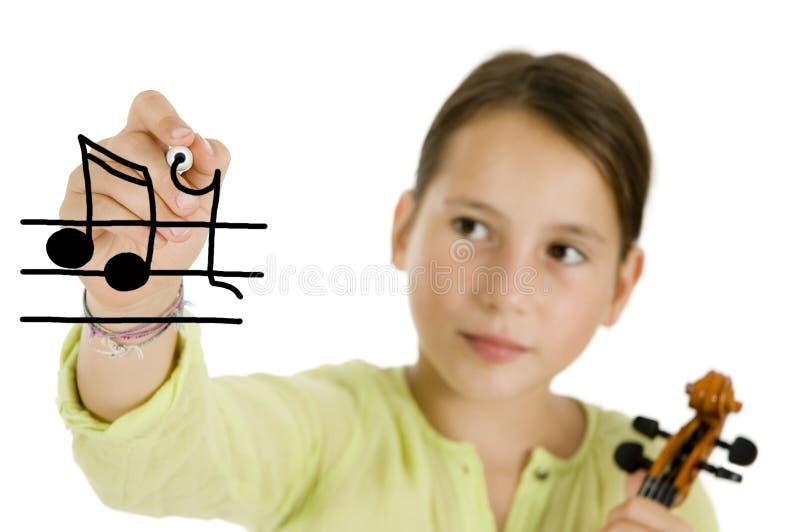 Mädchen, das eine Feder und eine Violine anhält stockfotografie