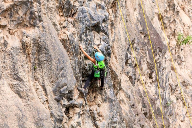 Mädchen, das eine Felsen-Wand klettert stockfotos