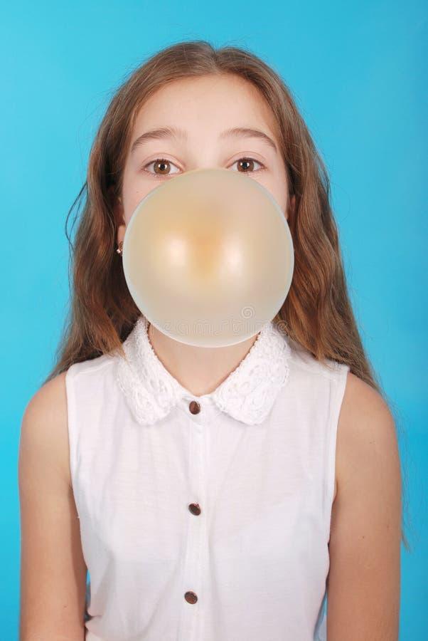 Mädchen, das eine große Kaugummiluftblase durchbrennt stockfotografie