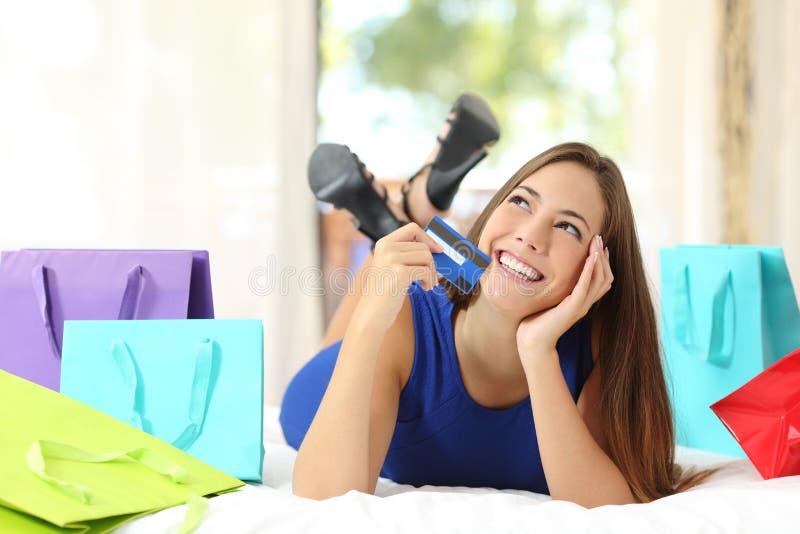 Mädchen, das eine Kreditkarte denkt was, zu Hause zu kaufen hält lizenzfreie stockfotografie