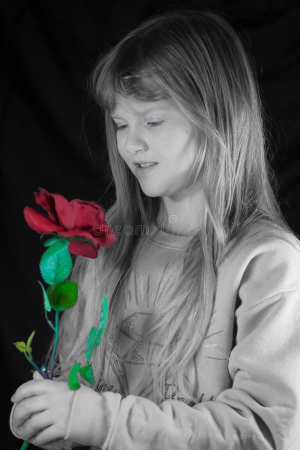 Mädchen, das eine Rose anhält. stockbild