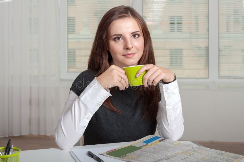 Mädchen, das eine Schale Grün nahe seinem Mund hält lizenzfreie stockfotografie