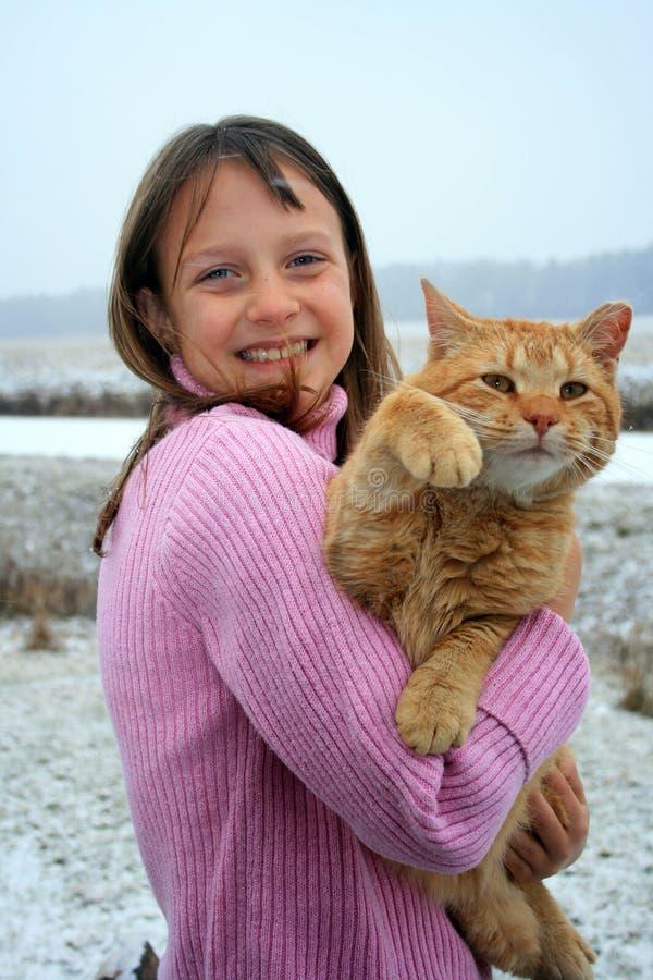 Mädchen, das eine wellenartig bewegende Katze anhält. lizenzfreie stockfotografie