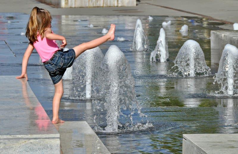 Mädchen, das in einem Brunnen spielt stockfotos