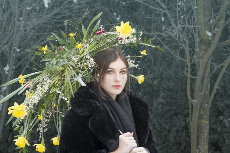 Mädchen, das einen Blumenregenschirm im Garten hält lizenzfreie stockfotos
