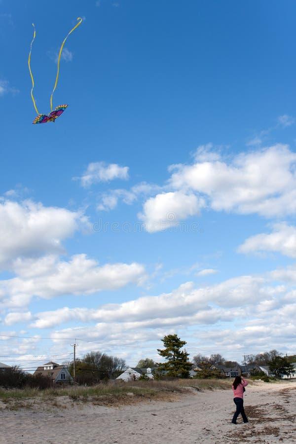 Mädchen, das einen Drachen am Strand fliegt lizenzfreie stockbilder