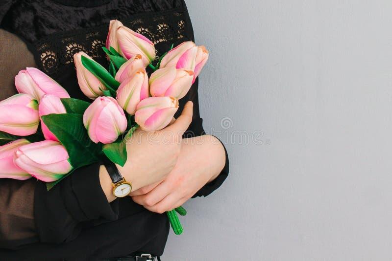 Mädchen, das einen enormen Blumenstrauß von rosa Tulpen in ihren Händen hält stockfotografie