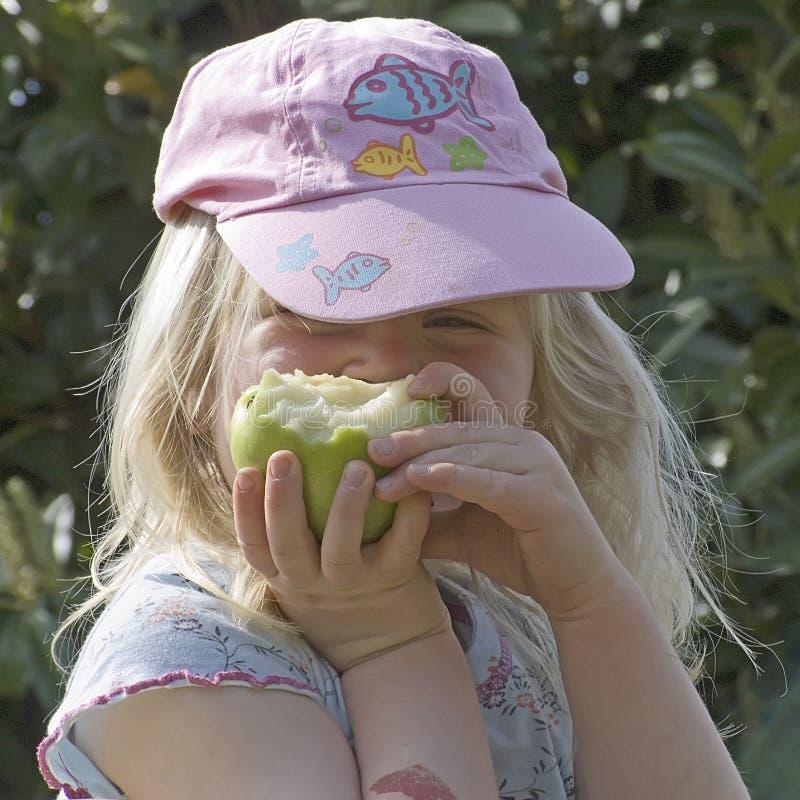 Mädchen, das einen grünen Apfel isst stockbild