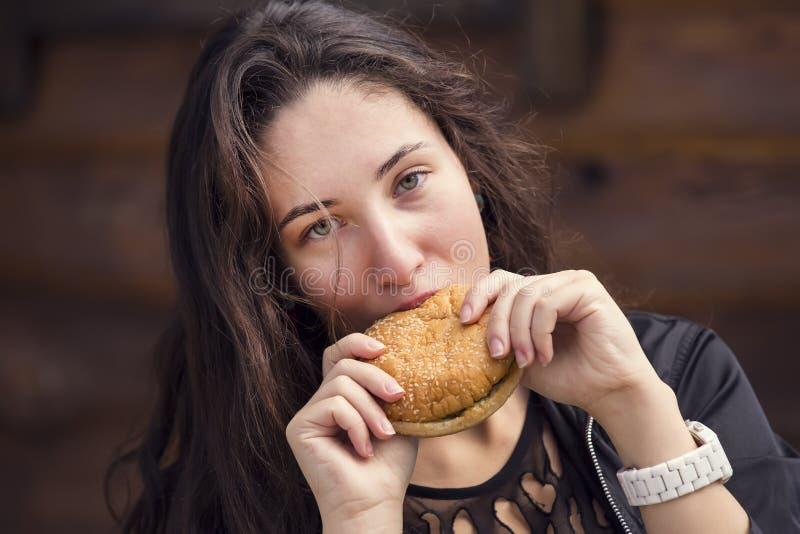 Mädchen, das einen Hamburger isst lizenzfreies stockbild