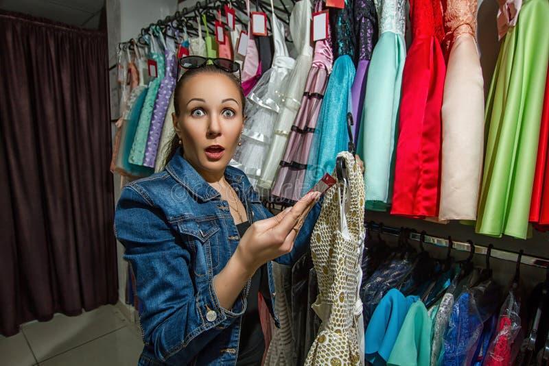 Mädchen, das einen Kauf von einem Kleid abschließt lizenzfreie stockfotos