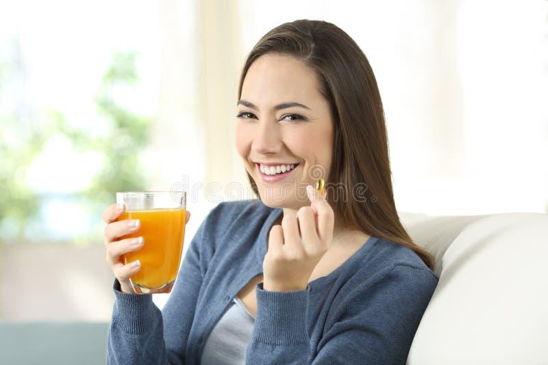 Mädchen, das einen Orangensaft und eine Pille Sie betrachtend hält lizenzfreie stockfotografie