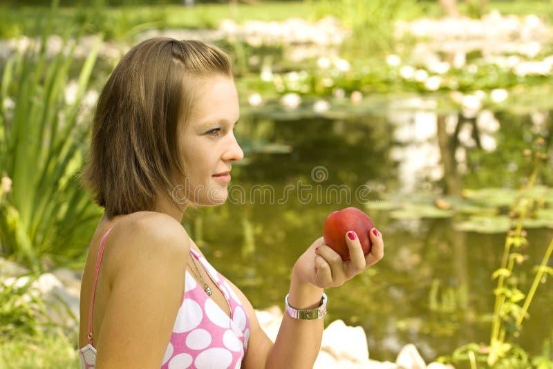 Mädchen, das einen Pfirsich anhält lizenzfreie stockfotos