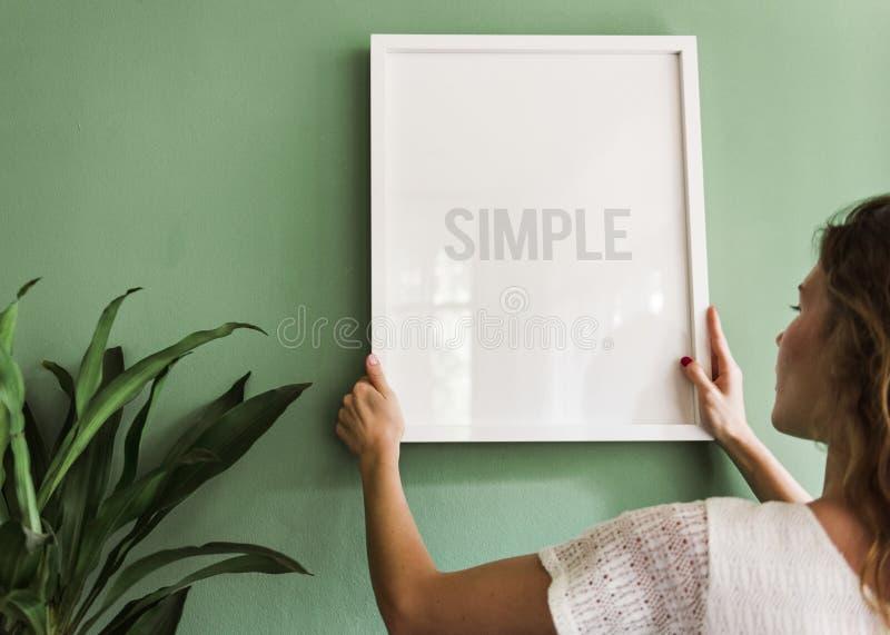 Mädchen, das einen Rahmen auf einer grünen Wand hängt lizenzfreies stockfoto