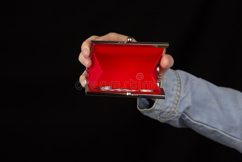 Mädchen, das einen roten Geldbeutel mit Münzen auf ihrer ausgestreckten Hand, Nahaufnahme, schwarzer Hintergrund hält stockfoto