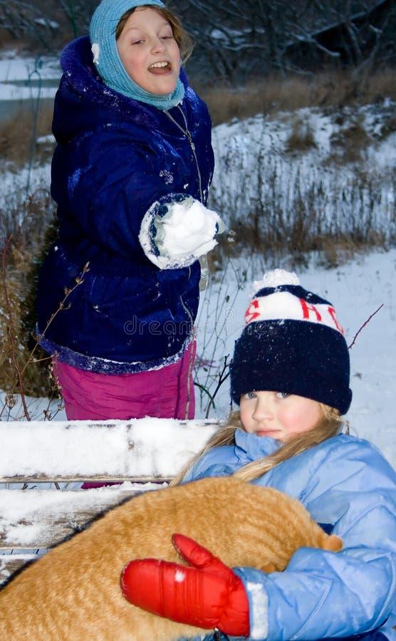 Mädchen, das einen Schneeball an einem anderen Kind wirft. stockfoto