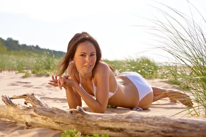 Mädchen, das einen Sonnenbrand auf dem Strand nimmt stockbild