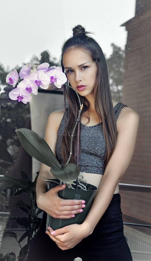 Mädchen, das einen Topf der Orchideenblume hält stockbilder
