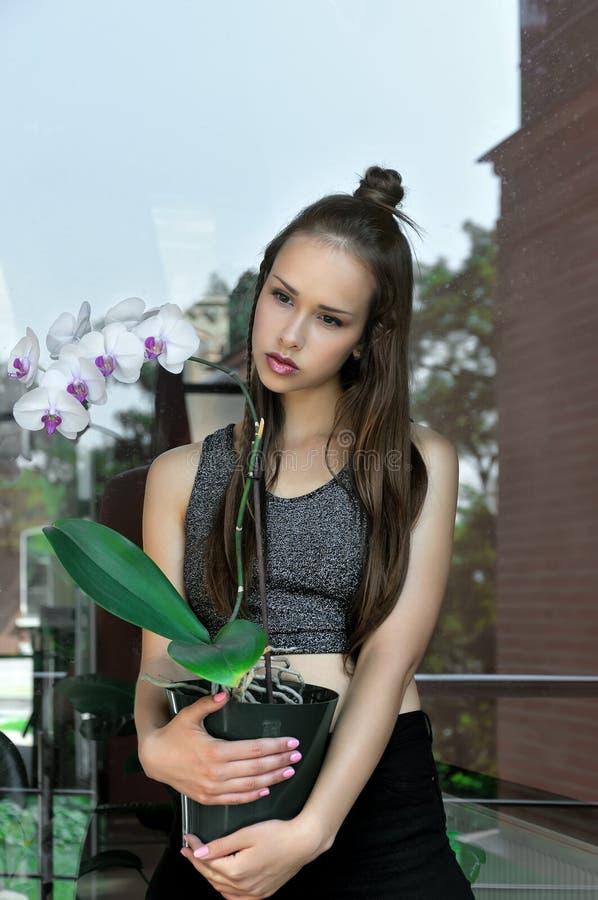 Mädchen, das einen Topf der Orchideenblume in ihren Händen hält lizenzfreie stockbilder