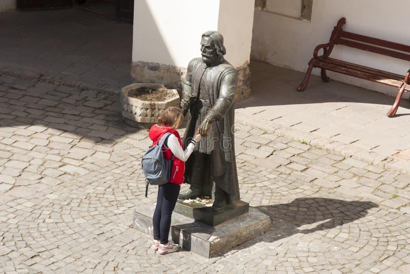 Mädchen, das einen Wunsch zur Statue von Prinzen Podolsky Fedir Koryatovych 1331-1414 im Schloss Palanok, Mukachevo, Ukraine-Foto lizenzfreies stockfoto