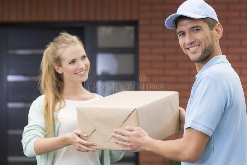 Mädchen, das einer Lieferungsform hübschen Kurier in der blauen Uniform nimmt lizenzfreie stockfotos