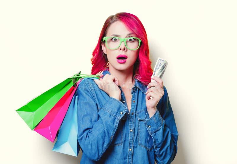 Mädchen, das Einkaufstaschen mit Geld hält lizenzfreies stockbild
