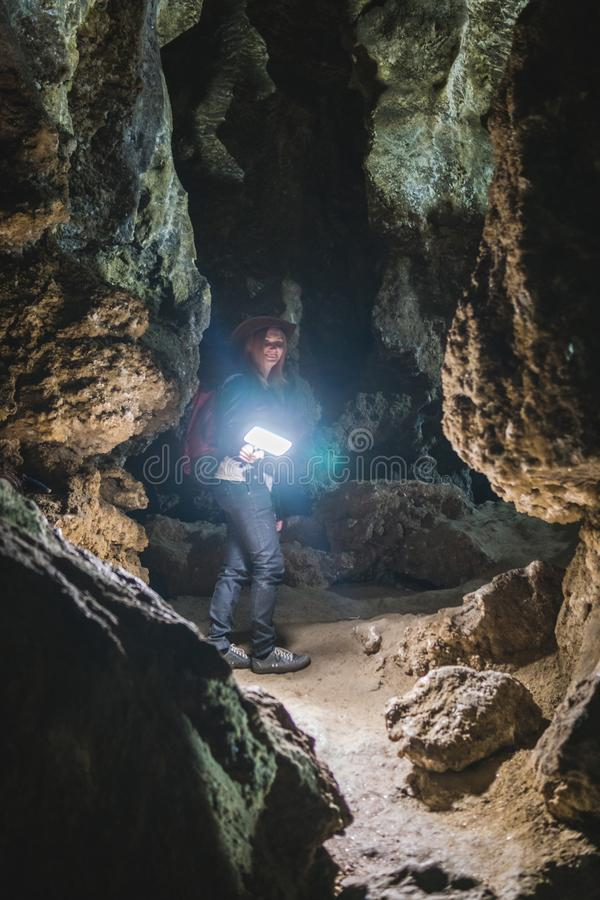Mädchen, das enorme Höhle erforscht Abenteuerreisender kleidete Cowboyhut und Rucksack, Lederjacke extreme Ferien, touristischer  stockbild